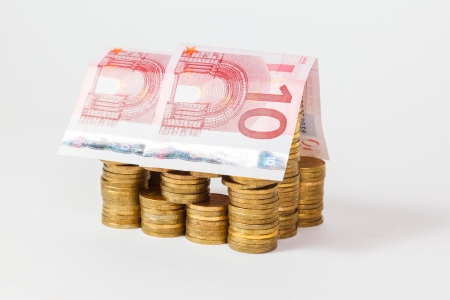 hypothec: house built of coins and euro banknotes on white background Stock Photo
