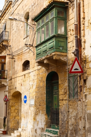 heads old building facade: green wooden front door to the house and balcony and facade in the Mediterranean