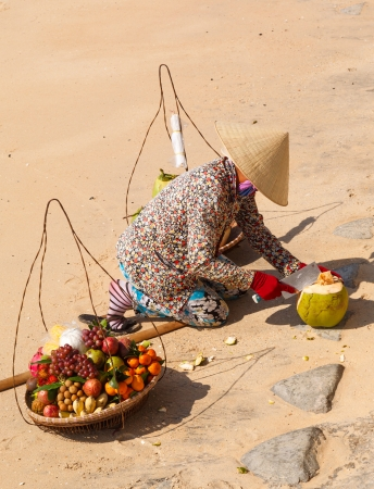 Vietnamese woman in a straw hat on the beach selling fruit and reveals the coconut photo