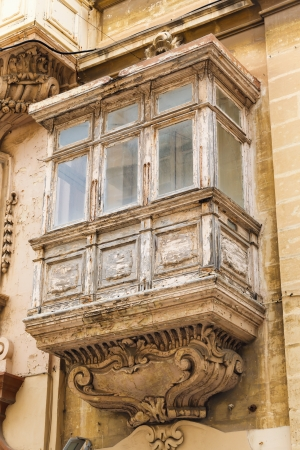 heads old building facade: old traditional wooden balcony and facade in the Valletta Malta