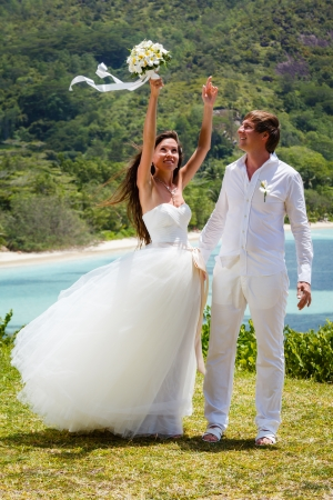 wedding bouquet of frangipani and newlyweds against the background the bay Seychelles photo