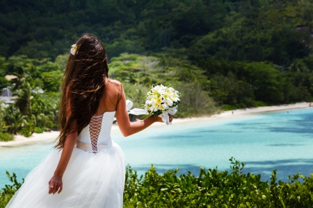 wedding beach: wedding bouquet of frangipani and groom against the background the bay Seychelles Stock Photo