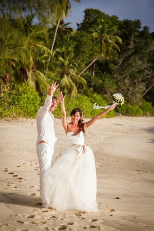 meaningful: newlyweds with wedding bouquet of jasmine on the beach in the Seychelles
