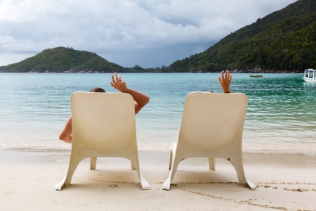 sunbeds on the beach in Seychelles and the couples hands with rings on a background cloudy sky