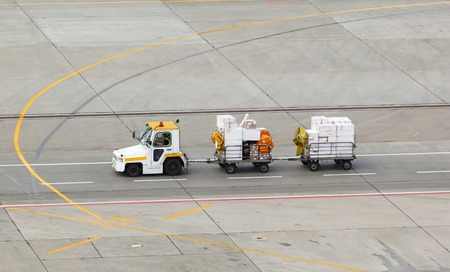 tug and luggage on the airport tarmac 写真素材