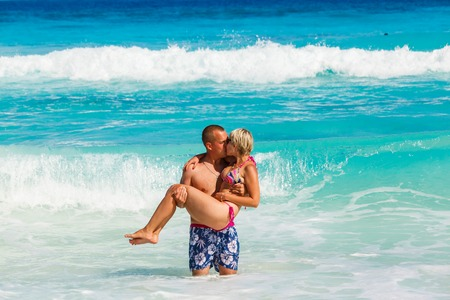 Young romantic couple (white young man and a young blonde girl with short hair wearing glasses) have fun on sandy beautiful tropical beach Seychelles La Digue photo