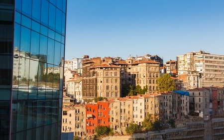 glass facade of a modern building and direct row of old colored houses in Istanbul on background blue sky photo