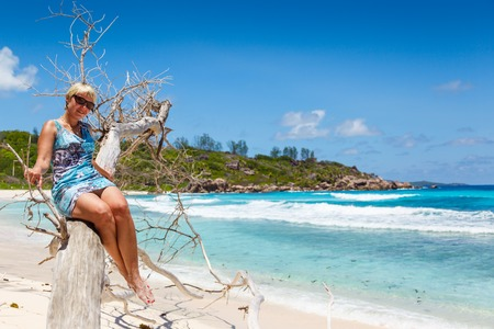 albero secco: ragazza in un abito su un albero secco sulla spiaggia di La Digue Seychelles