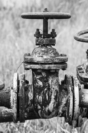 Old rusty valves closeup at an abandoned oil refinery black and white photo