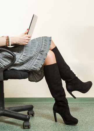 office work, beautiful legs and skirt of a young girl working on laptop photo