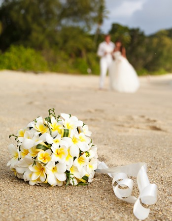 wedding bouquet of jasmine or frangipani with newlyweds on the beach in the Seychelles