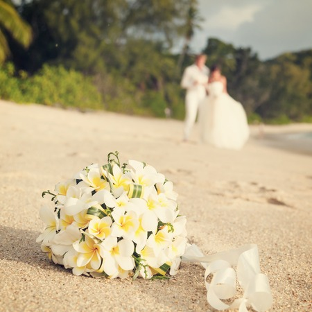 wedding bouquet of jasmine or frangipani with newlyweds on the beach in the Seychelles photo