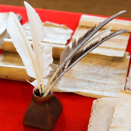 inkpot: feathers and inkpot with Old books on the red tablecloth Stock Photo