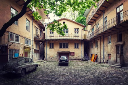 rusty car: black vintage car and old rusty car in the old courtyard of the city Lviv Stock Photo