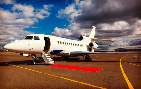 private plane: White reactive private jet, the front landing gear and a ladder on blue sky and clouds