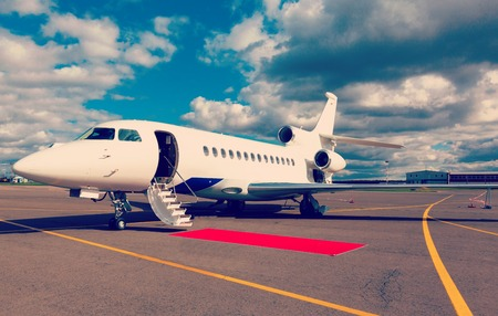 White reactive private jet, the front landing gear and a ladder on blue sky and clouds photo