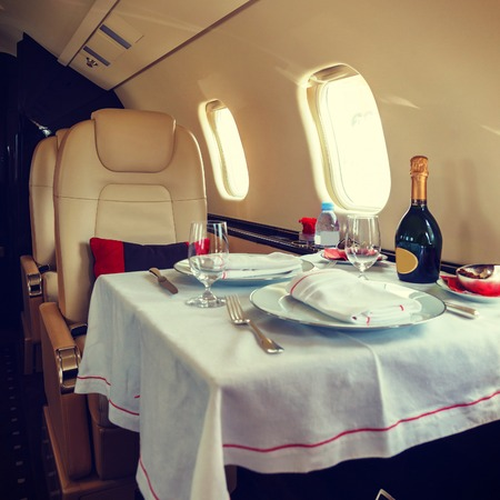first plane: Luxury interior aircraft business aviation decorated table Stock Photo