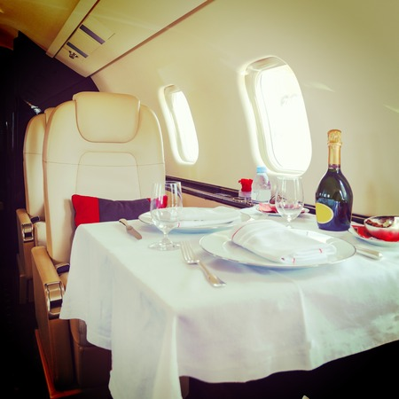 Luxury interior aircraft business aviation decorated table Stock Photo
