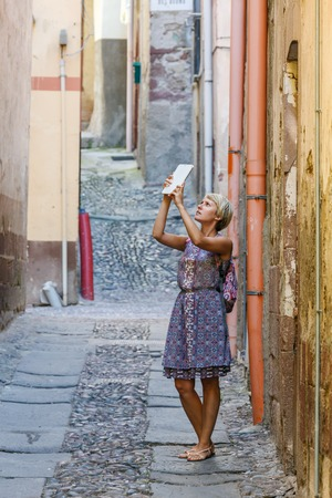 young girl tourist with blond short hair wearing a bright dress uses a tablet, in old town Sardinia Italy photo
