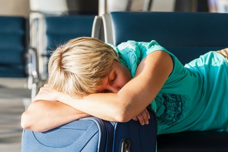 beautiful young woman with blond short hair with a suitcase sleep on a chair at the airport and waiting for her flight