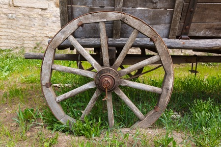 Old wooden cartwheel with rusty steel rim and green grass closeup photo