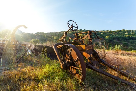 Antique Farm Equipment and Old hay rake at sunrise, Italy