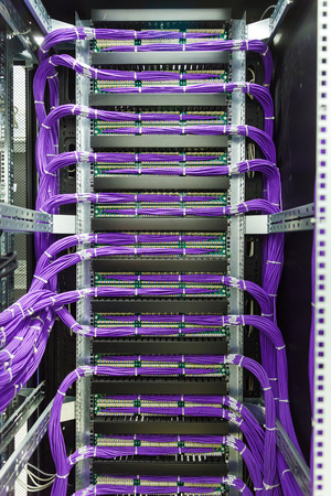 Large group of lilac utp Internet cables in rack data center Stock Photo