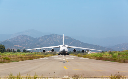 White heavy cargo jet with four engines ready to take off in the airport on background of mountains Stock Photo