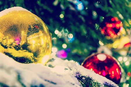 Red and yellow Christmas balls on a snow covered branch Christmas tree photo