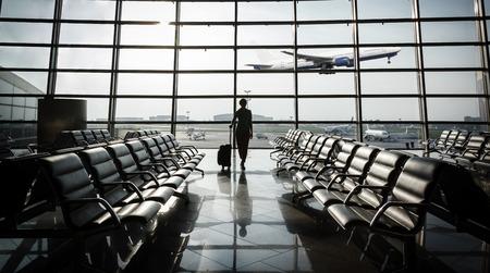 maletas de viaje: hermosa mujer joven con el pelo corto rubio con una maleta en el aeropuerto y en espera de su vuelo y avi�n despegando