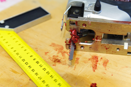 power tools: safety advice while operating power tools. Blood on the blade of the saw jigsaw on the board near a ruler Stock Photo