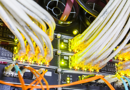 rack in the data center with working servers with optical and UTP cables