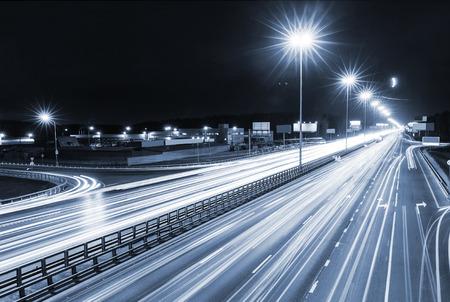 モスクワの夜メトロポリス、トラフィックおよび多車線のハイウェーおよび密な道路交通上の車のぼやけたライトを輸送します。 写真素材