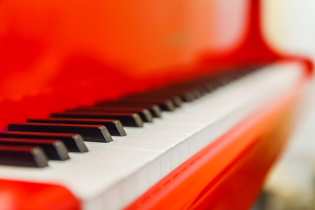 piano closeup: white and black keys of red piano closeup Stock Photo
