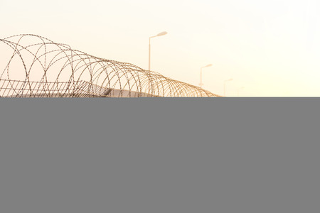 chain fence: fence with barbed wire on the border of the object at dawn with fog in the summer, russia