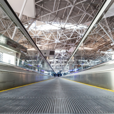 travelator at the airport and a metal roof and blurred lights Stock Photo