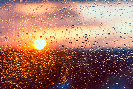 sunny season: Water drops on a window glass after the rain. The sky with clouds and sun on background. Stock Photo