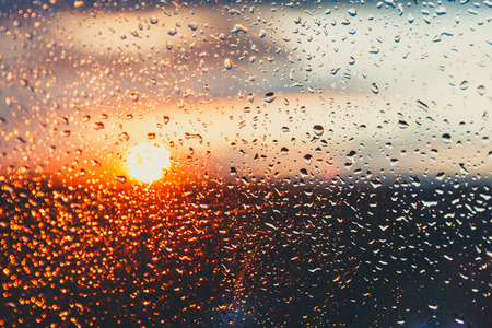 Water drops on a window glass after the rain. The sky with clouds and sun on background. Stock fotó