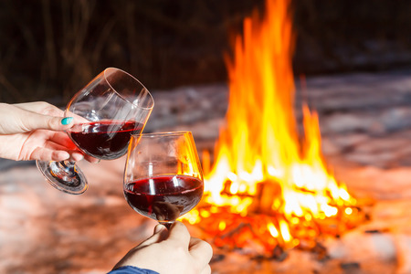 vin chaud: Jeune couple près du feu de joie avec deux verres de vin rouge Banque d'images