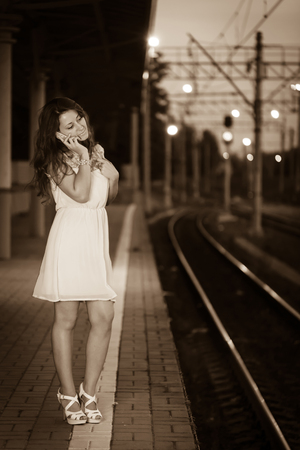 Portrait of young pretty smiling girl at summer weather dressed in a bright dress talking on the phone at a train station 版權商用圖片