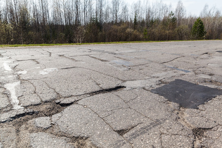 pot hole: Holes and cracks in the asphalt road on bad broken in Russia Stock Photo