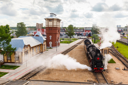 peron: old black steam locomotive in Russia at the summer at the old railway station