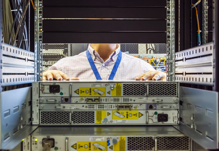 data center data centre: IT Engineer installs equipment in the rack in datacenter Stock Photo