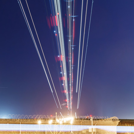 lights of aircraft on the glide path during night landings Stock Photo