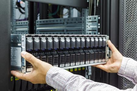 IT Engineer installeert apparatuur in het rek in datacenter Stockfoto
