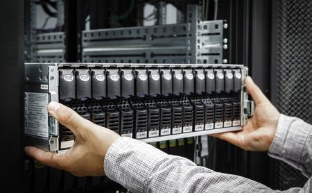IT Engineer installs equipment in the rack in datacenter Stock fotó