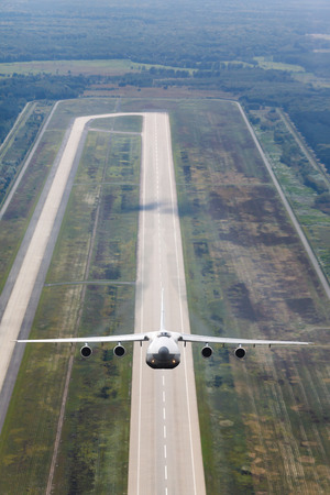 airstrip: white jet cargo plane takes off from the runway on the background of airstrip