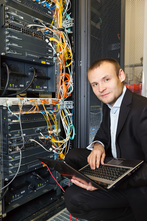nas: IT Engineer working on a laptop lying in the rack in datacenter