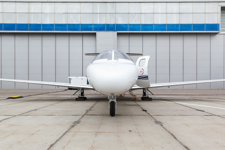 peron: White reactive private jet, the front landing gear and a ladder on concrete Peron