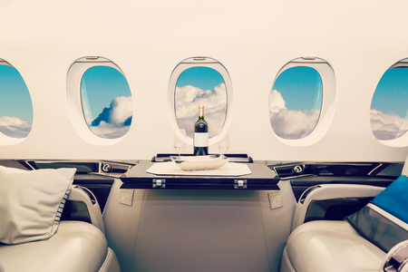 Luxury interior in bright colors of genuine leather in the business jet, sky and clouds through the porthole Standard-Bild